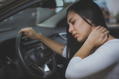 Woman grabbing her neck in pain of whiplash from being rear-ended by another vehicle.